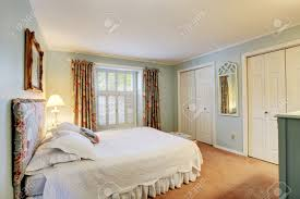 soft tones bedroom with light blue walls and brown carpet floor
