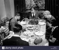 1940s three generation family saying grace thanksgiving dinner