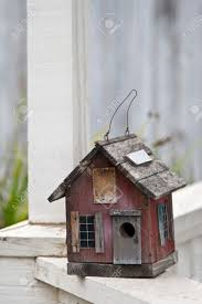 country folk style bird house on front porch railing stock photo