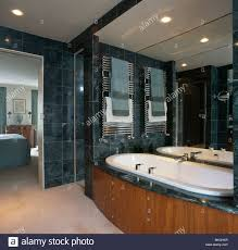 En Suite Bathrooms by Towels On Heated Towel Rails Above Bath In Modern Marble Tiled