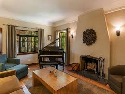 traditional living room complement with piano and wall sconces and