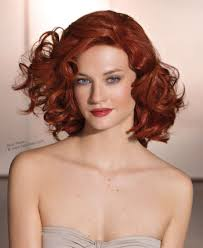 red hair with curls cut at shoulder length and styled to the back