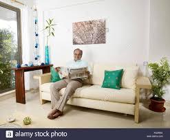 old man reading newspaper sitting on sofa mr 702t stock photo