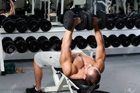 young bodybuilder training in the gym dumbbell bench press