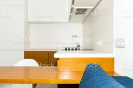 kitchen cabinet design for small apartment modern wooden brown orange kitchen cabinets in small apartment studio bar stool counter interior design and nobody on blue sofa in minimalist home
