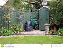 garden shed in an english garden with compost bin stock photos