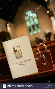 wedding gift next a traditional decorative order of service card next to small gift