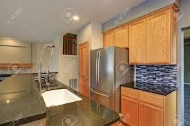 what backsplash goes with light wood cabinets small compact kitchen room with light wood cabinetry quartz