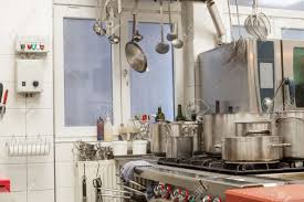 neat interior of a commercial kitchen with wall mounted utensils