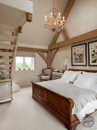 master bedroom with mezzanine staircase and exposed timber frame