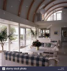 white sofas in a large double height living room with a mezzanine