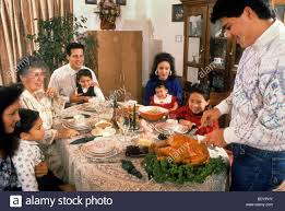family watches carve turkey thanksgiving meal celebrate