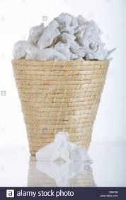 wicker waste paper basket bin full of used tissues with single