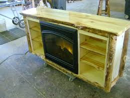 custom aspen log tv stand with a built in electric fire place by