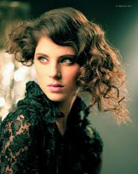 short hairstyle with curls and added length on one side created