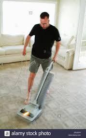 man vacuuming carpet in house stock photo royalty free image