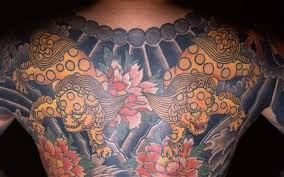 a yakuza gang member wears a tattoo of shisa a cross between a