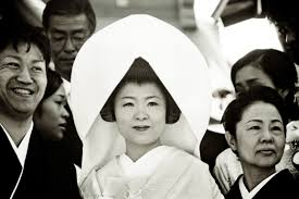 a japanese bride in traditional shinto wedding dress stands with