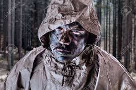 a soldier wearing a poncho o raincoat and army camouflage face
