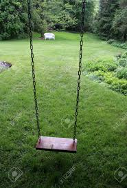 Swings For Backyard An Old Wooden Swing Sitting In A Lush Backyard Stock Photo