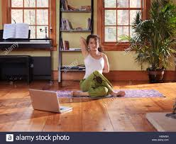 Livingroom Yoga Woman Practicing Yoga In Front Of A Laptop Computer At Home In A