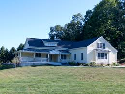 craftman style farmhouse with huge wraparound porch metal roof