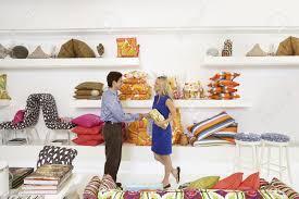 salesman in home furnishings store shaking customer u0027s hand stock