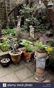 hidden treasure paved patio trellis potted plants statues small