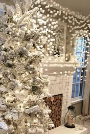 white christmas tree with snow and white baubles completed by