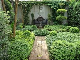 astonishing spanish courtyard garden with black iron bench and