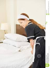 hotel maid making bed during housekeeping stock photo image