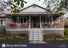grey country cottage style home facade with veranda in autumn