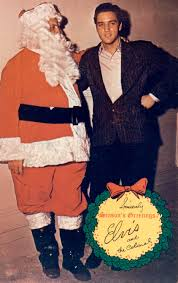 this photo shows elvis with santa claus colonel parker behind