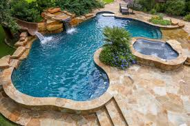 beach entry swimming pool with a slide and waterfall backyard