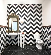 contemporary powder room features walls clad in black and white