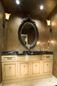 oval black wooden bathroom mirror with brown carving accent on the