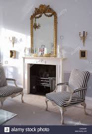 Stuffed Chairs Living Room by Antique Gilt Mirror Above White Fireplace In Living Room With