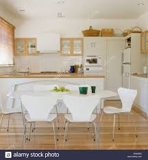 white arne jacobsen ant chairs in modern white kitchen dining room