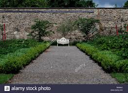 gravel path leading to a white wrought iron metal garden seat in a