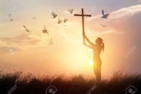 praying with cross and flying bird in nature sunset