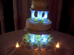 cake pillars wedding cake with room dimmed showing cake lit candles cup