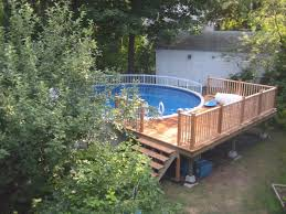 circle white pool with brown wooden pol deck having brown wooden