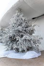 large tree decorated with silver ornaments and coverd