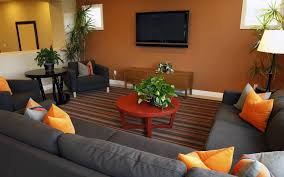 Led Tv Table Decorations Grey Fabric Sofa And Orange Grey Cushions Connected By Round Brown