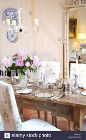 vase of pink peonies on table set for dinner in country dining