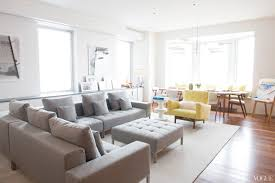 beyond neutral color palette living the serene life in nyc white gray color palette interior design grey sectional sofa yellow side chair modern new york city