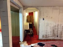 a photo of our basement after i put primer on the wood paneling