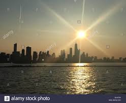 sun with rays setting chicago view from lake michigan in summer