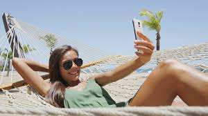 hammock bed beach woman taking smartphone selfie picture relaxing on holiday