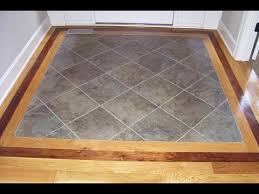 hardwood floor with tile inlay at entryway